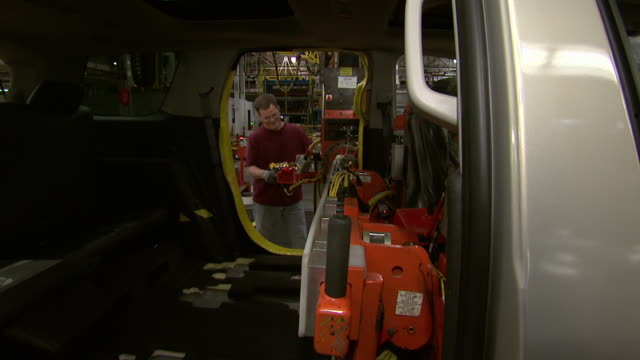 vídeos de stock e filmes b-roll de november 19 2008 zi car shell moving on assembly line as worker is inserting seat using robotic arm / lansing michigan united states - general motors