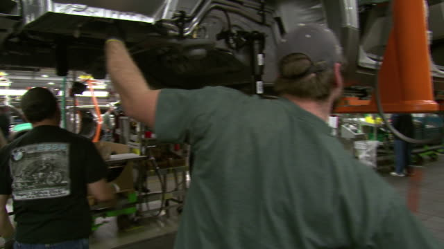 november 19 2008 ms factory workers under car on assembly line / lansing michigan united states - lansing stock videos and b-roll footage