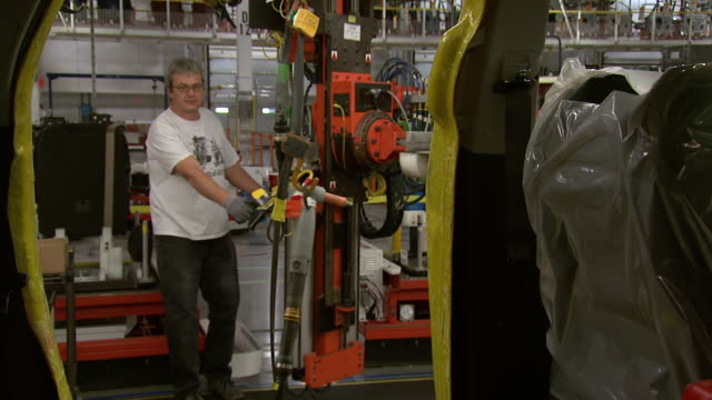 november 19 2008 ms gm plant worker using a mechanized lift installing rear passenger seats in an automobile on the assembly line / lansing michigan... - lansing stock videos and b-roll footage