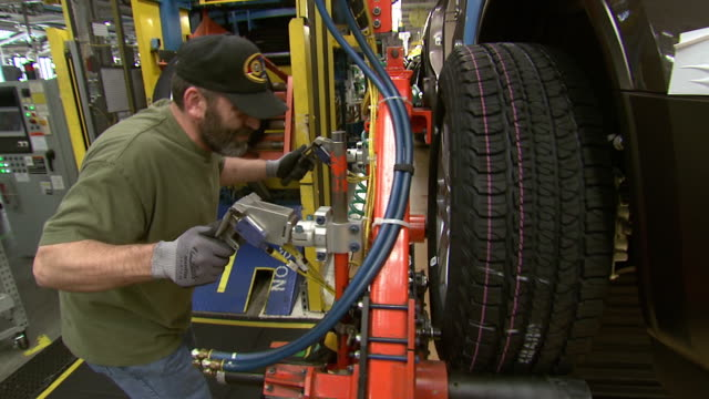 november 19 2008 ts worker mounting car tire on automated assembly line at general motors plant / lansing michigan united states - lansing stock videos and b-roll footage