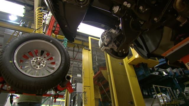 november 19 2008 la worker mounting new tire on car on assembly line / lansing michigan united states - lansing stock videos and b-roll footage