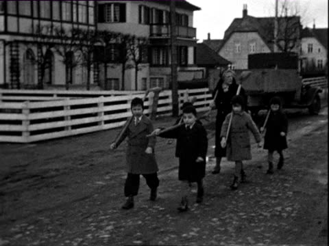vídeos de stock, filmes e b-roll de november 1932 b/w ws pan ms children walking down road, carrying shovels / wyk auf fohr, nordfriesland, germany - capa de chuva