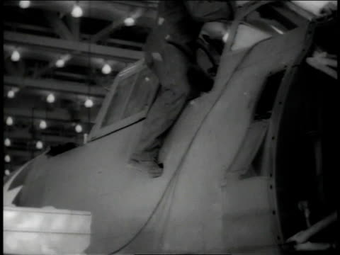 November 1942 LA Man getting into cockpit of plane while another man is loading a box into a side compartment / Long Beach, California, United States