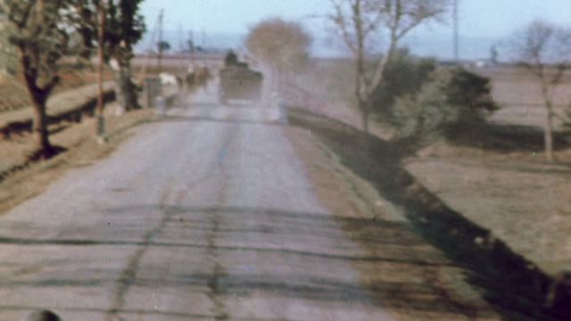 vídeos de stock e filmes b-roll de november 1942 montage us army tank convoy traveling on one lane desert roads to the tunisian front with jeep leading the way and tank barrel's shadow... - 1942