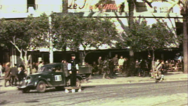 vídeos de stock e filmes b-roll de november 1942 pan us army soldiers and civilians walking and driving on the city streets with an american flag flying outside a hotel appropriated as... - 1942