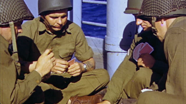 November 1942 HA US Army soldiers in desert battledress playing cards on ship deck with one removing his helmet to reveal a short Mohawk haircut