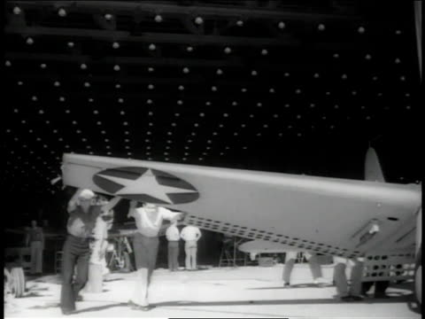 November 1942 LA Workers pushing and turning assembled plane in the factory by the wing / Long Beach, California, United States