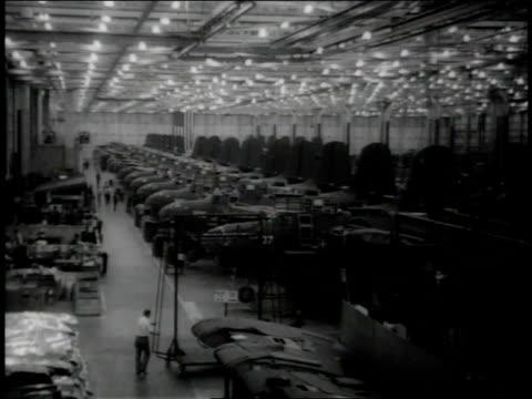 November 1942 HA Workers pushing cart around assembly line at aircraft factory / Long Beach, California, United States