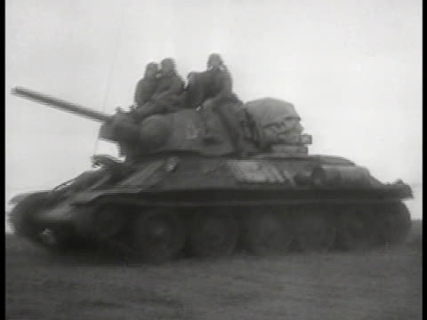 november 1943' superimposed over coastline. russian soldiers riding on t-34 medium tank. t-34 tanks moving on hilly field, bombs exploding. fast... - tank stock videos & royalty-free footage