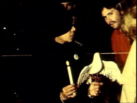 vidéos et rushes de november 1969 woman holding fake dove at a candlelight vigil / washington, d.c., united states - 1969