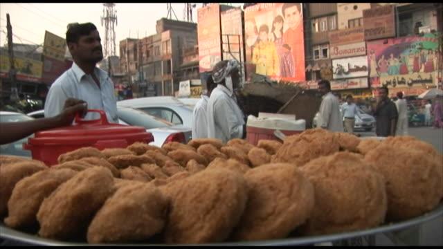 vidéos et rushes de november 2, 2005 tray of bread in outdoor marketplace with merchants behind / lahore, pakistan - lahore pakistan