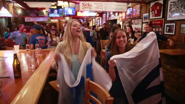 vídeos de stock, filmes e b-roll de november 2 2016 bloomington indiana usa chicago cubs fans adrienne arlan left and nicole slivensky hold w flags and sing go cubs go to celebrate... - bloomington indiana
