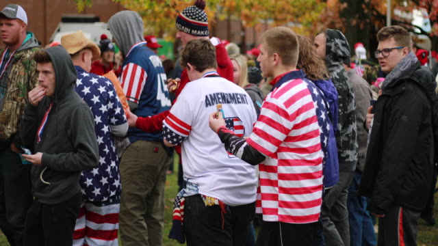 Fans and supporters of United States President Donald J Trump wearing American flag shirts while they wait in line outside Southport High School...