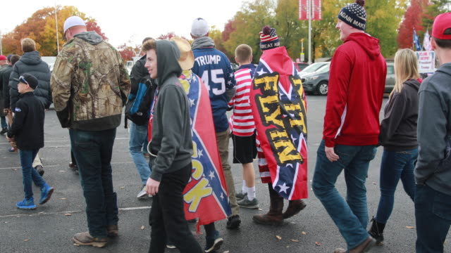trump supporters wearing american and confederate flags while waiting in line before president trump arrives to speak during a political rally at... - ヒルビリー点の映像素材/bロール