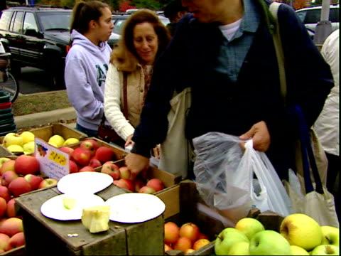 november 20, 2007 man selling and cutting up apples at a farmer's market / mt. vernon, virginia, united states - バージニア州マウントヴァーノン点の映像素材/bロール