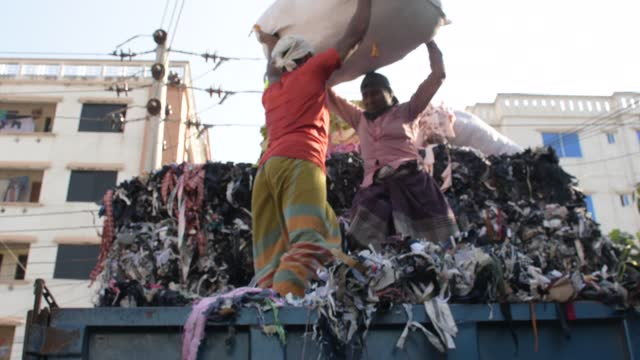november 2020: workers load a truck with garment leftovers as waste at mirpur area in the capital city of dhaka, bangladesh on november 13, 2020. - garment stock videos & royalty-free footage