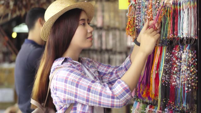 november 20,2018:bangkok thailand ; beautiful asian woman shopping on the chatuchak weekend market in the thailand vacation choosing choosing new clothes, looking through hangers with different casual colorful garments on hangers, shopping concept  for he - wardrobe stock videos & royalty-free footage