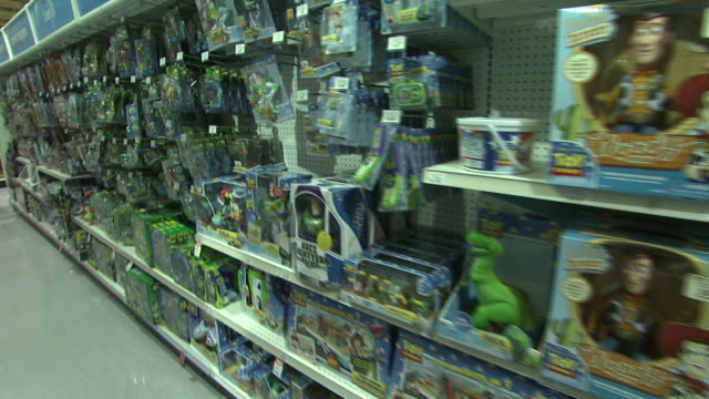 november 24, 2009 display racks and shelves with toys and action figures in plastic packaging at toys r us / united states - negozio di giocattoli video stock e b–roll