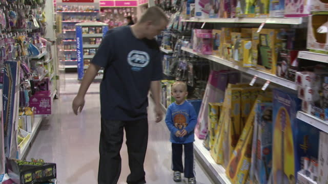 november 24, 2009 father and daughter perusing toys r us store aisles looking at toys / united states - negozio di giocattoli video stock e b–roll