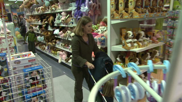 november 24, 2009 mother and children browsing through toys r us and passing racks of stuffed animals / united states - negozio di giocattoli video stock e b–roll