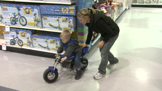 stockvideo's en b-roll-footage met november 24 2009 ts shopper pushing child on minimotorcycle through aisle of toys r us / united states - toys r us