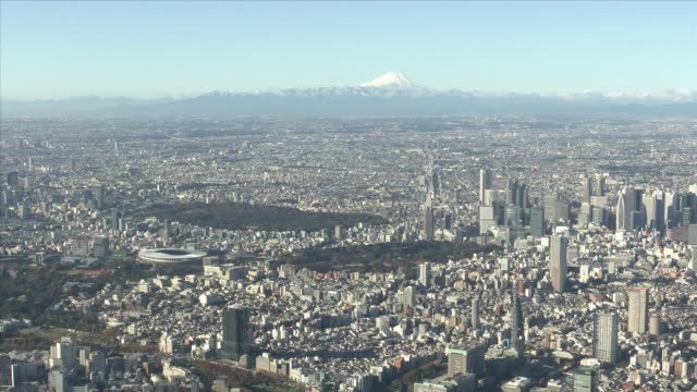 november 29 aerial shot of tokyo skyline with snowcapped mount fuji and japan national stadium also called olympic stadium the stadium was completed... - tokyo japan stock videos & royalty-free footage