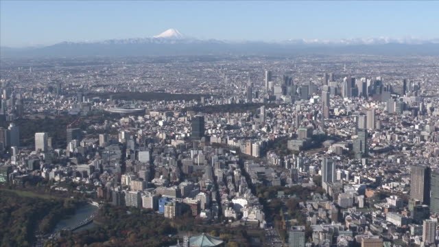november 29 aerial shot of tokyo skyline with snowcapped mount fuji and japan national stadium, also called olympic stadium; the stadium was... - trefferversuch stock-videos und b-roll-filmmaterial