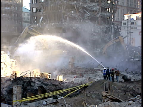 november 6 2001 montage ground zero clean up operations with firemen spraying the debris and a backhoe digging / new york city new york united states - 2001年点の映像素材/bロール