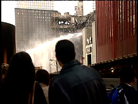 november 6, 2001 pedestrians and tourists standing on a city street and looking up at the still smoking remains of the world trade center as water is... - 2001 stock videos & royalty-free footage