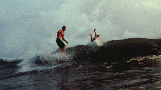 vídeos de stock, filmes e b-roll de november 6 2007 montage a surfer carving mellow waves on a long board at sunset - passear sem destino