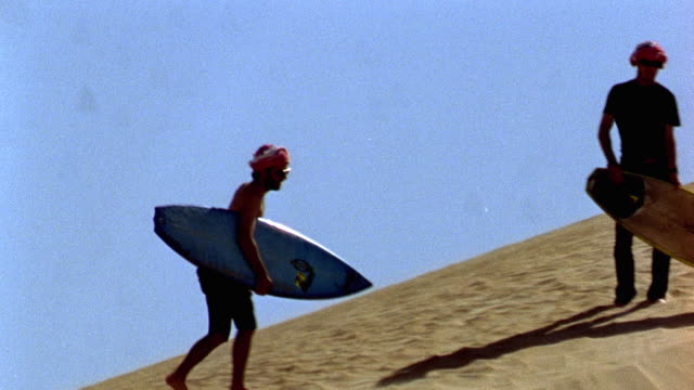 november 6 2007 montage surfers riding down sand dunes on short boards / oman - 2007 stock videos & royalty-free footage