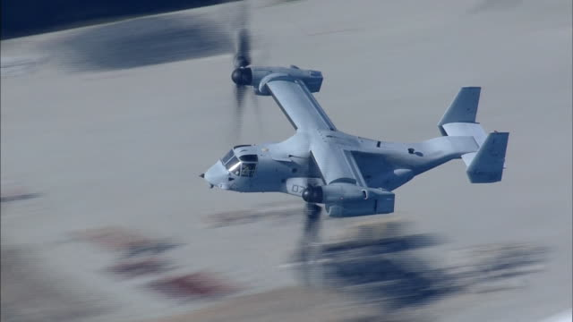 stockvideo's en b-roll-footage met november 8 2014 aerial shot of an american military aircraft mv22 called osprey flying in the air above the ocean during the disaster drill... - visarend