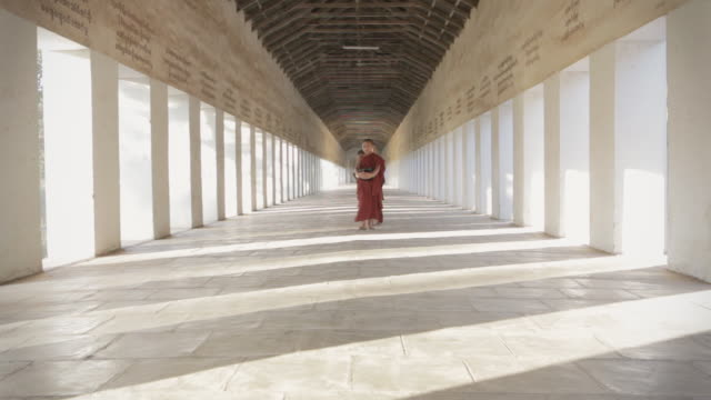 WS Novice Buddhist monks walk through a temple corridor with alms bowls / Bagan, Myanmar