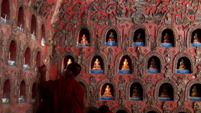 novice monks lighting candles for buddha hdv220 - myanmar stock videos and b-roll footage