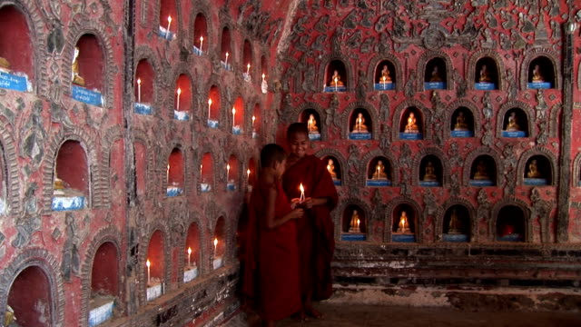 novice monks lighting candles for buddha hdv221 - myanmar stock videos and b-roll footage