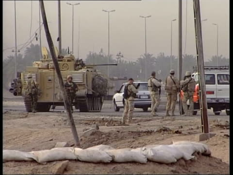 nr basra: ext gv british tank next basra city gates on riverbank statue of saddam hussein armoured vehicle next statue at city gates british soldiers... - major road bildbanksvideor och videomaterial från bakom kulisserna