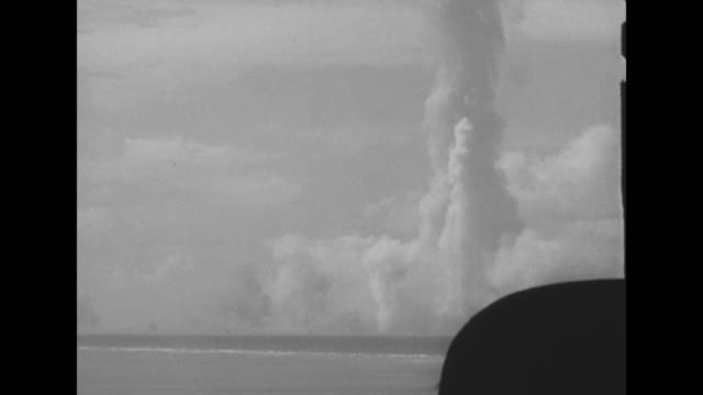 nuclear bomb explosion at sea off bikini / large mushroom cloud forming / ship behind dissipating cloud / base of forming mushroom cloud when... - 大量破壊兵器点の映像素材/bロール
