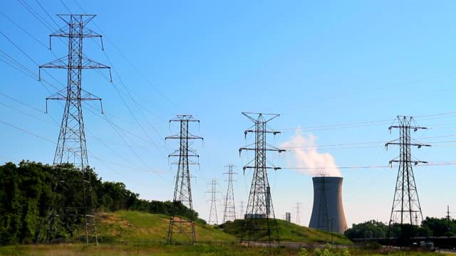 vídeos de stock e filmes b-roll de nuclear torre de arrefecimento com torres de transmissão - urânio
