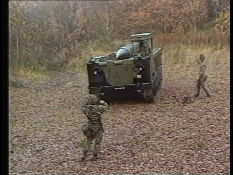 stockvideo's en b-roll-footage met nuclear deployment itn lib tms armoured vehicle carrying lance missile directed along by troops cms soldier directs cms soldier turning handle to... - raket wapen