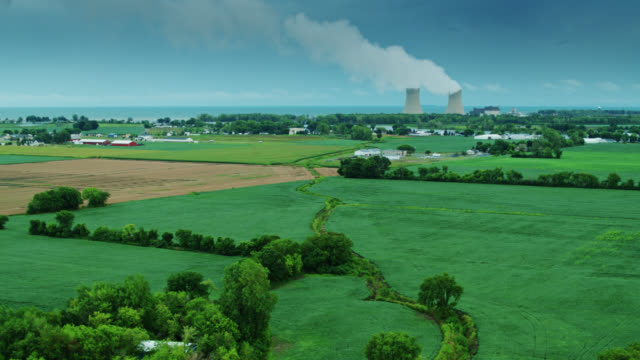 nuclear power plant steaming over lake erie and rural michigan landscape - drone shot - power station stock videos & royalty-free footage