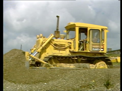 nuclear power station capacity in the uk lib suffolk sizewell b site ext cms bulldozer pushing earth rl pull out tms surveyor with pole on site pan... - b rolle stock-videos und b-roll-filmmaterial