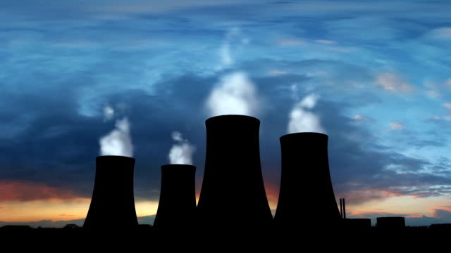 nuclear power station with steaming cooling towers silhouette - nuclear reactor stock videos & royalty-free footage