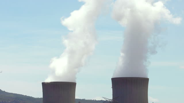 nuclear power station with water steam chimneys and blue sky in spain. - fissione nucleare video stock e b–roll