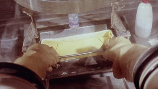 1957 montage nuclear technicians working in glove boxes with strict precautions when dealing with fissile uranium 235 / capenhurst, cheshire, england - nuclear energy stock videos & royalty-free footage