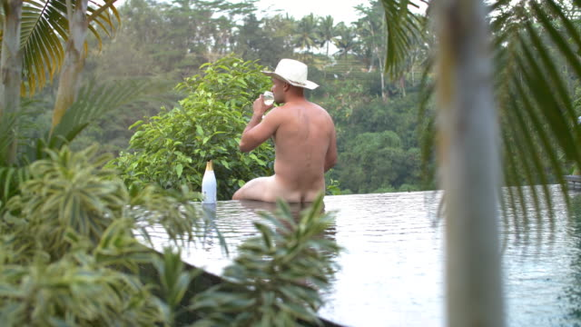nude male relaxing at pool - naturist stock videos & royalty-free footage