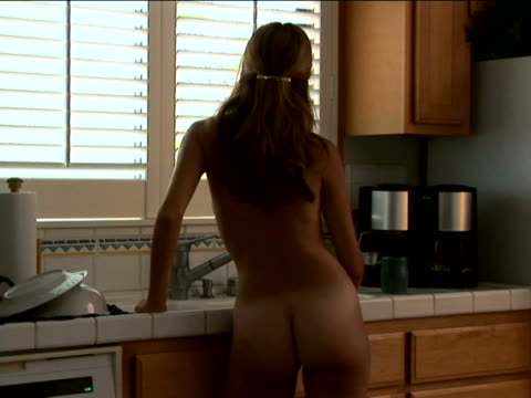 Nude woman in kitchen