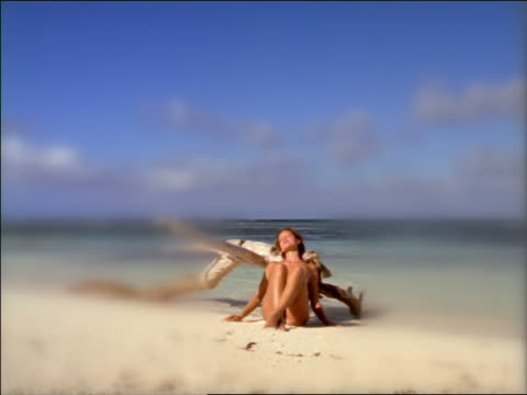 SELECTIVE FOCUS nude woman sitting with back to large piece of driftwood on beach getting tan