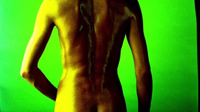 vídeos de stock, filmes e b-roll de yellow overexposed nude woman's back turning towards + away from camera / green background - superexposto