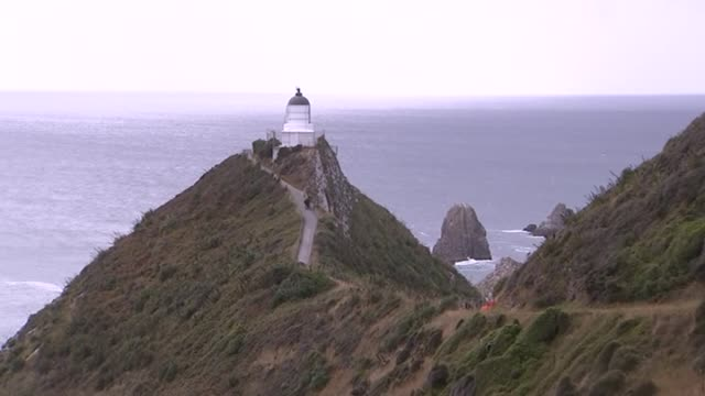 vídeos de stock e filmes b-roll de nugget point lighthouse with long track along cliff top in the catlins in southland new zealand - vista geral