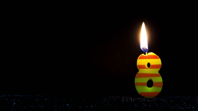 number shaped colorful candle burning - numero 8 video stock e b–roll